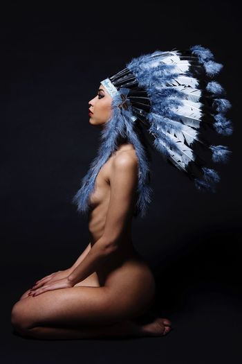 Side View Of Naked Woman Wearing North American Tribal Headdress Against Black Background