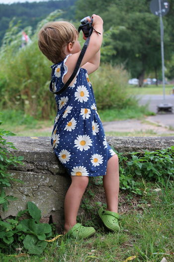 Full length of girl playing with camera on field