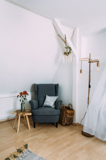 Empty chairs against white wall at home
