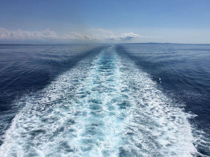 Wake in sea against sky