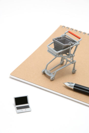 High angle view of toy laptop by shopping cart and spiral notebook against white background