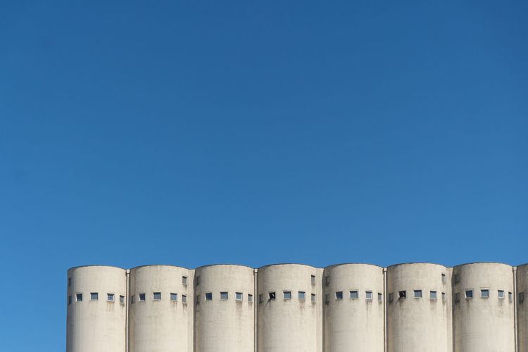Copy Space Clear Sky No People Blue Side By Side In A Row Low Angle View Factory High Section Pattern Silo Building Exterior Architecture Minimalism Windows Seven Run-down Circle Dockyard Parallel Simplicity Backgrounds