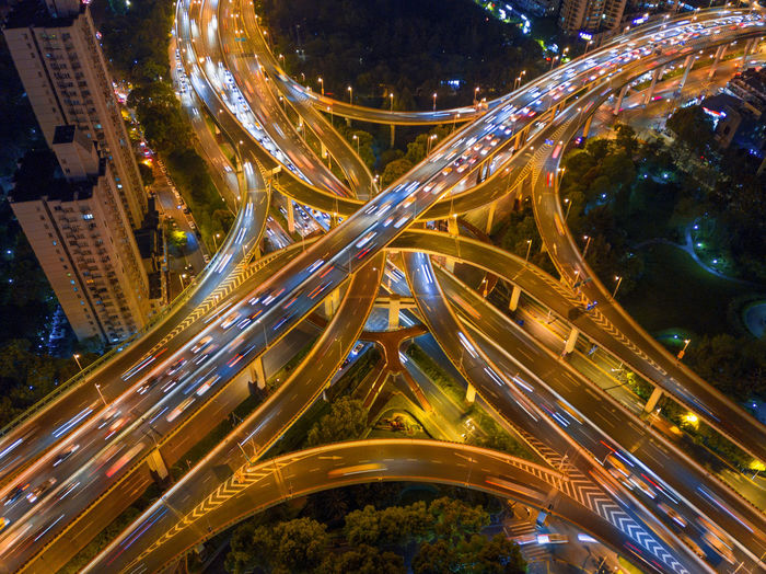 Aerial view of light trails on elevated road in city at night
