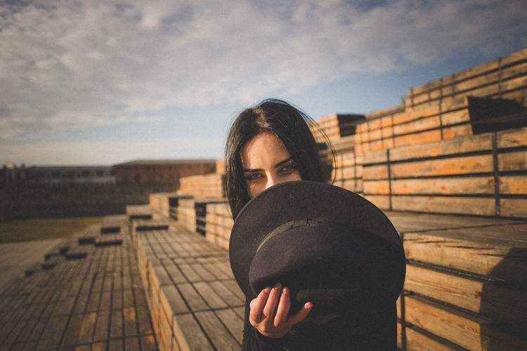 Portrait of beautiful young woman holding hat sitting on wood