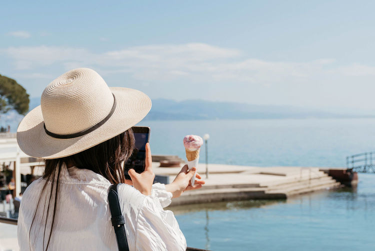 Rear view of young woman taking photos of ice cream in cone in shore of sea.