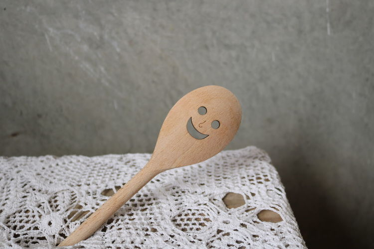 Close-up of smiley face on wooden spoon against wall