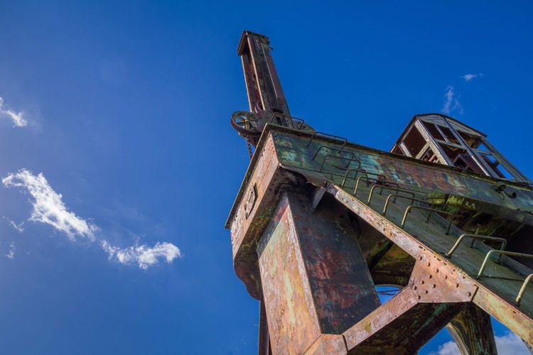 Low Angle View Of Old-Fashioned Crane Against Blue Sky