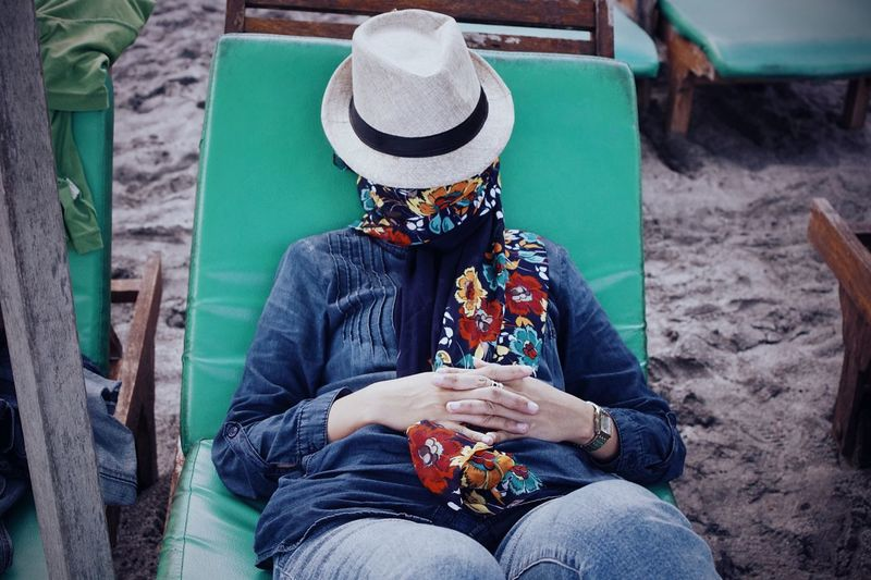 High angle view of woman face covered with hat while lying on lounge chair