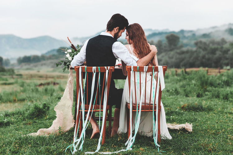 Rear view of wedding couple sitting on chairs at farm