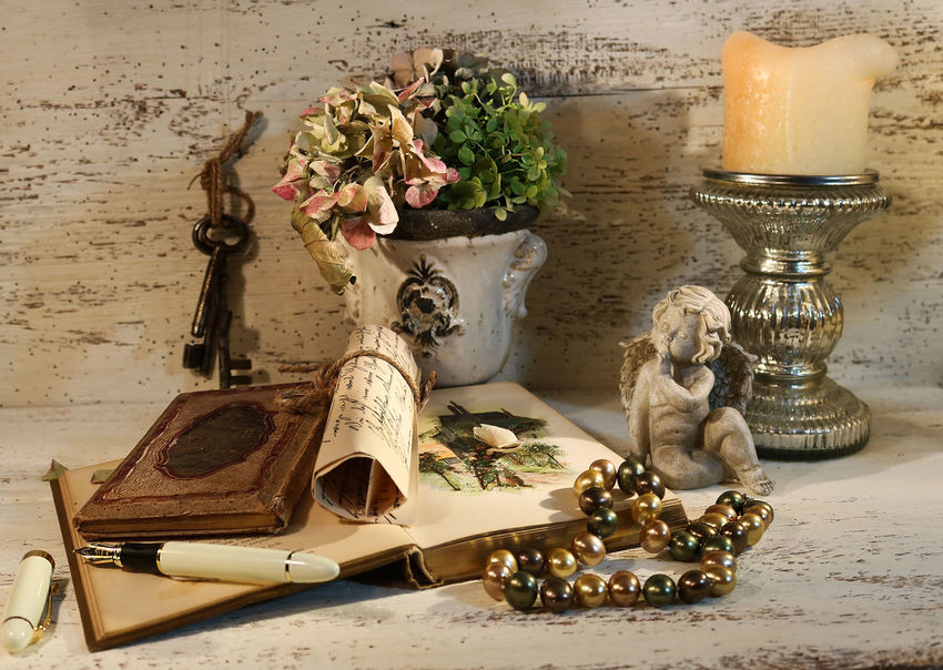 Indoors  Still Life Table Flower Decoration Sculpture Antique Large Group Of Objects Angel Sculpture Pearls Old Books Candle Candle Holder Silver Classic Still Life