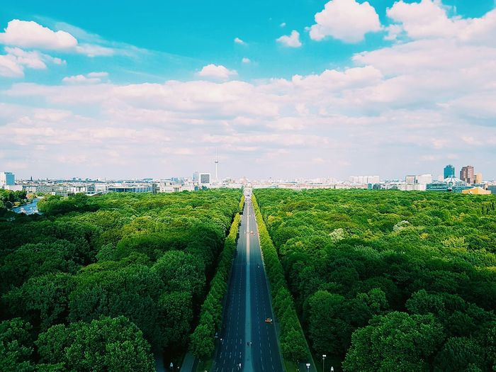 High Angle View Of Street Amidst Trees Towards City Against Cloudy Sky
