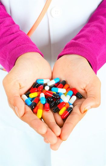Midsection of doctor holding colorful capsules