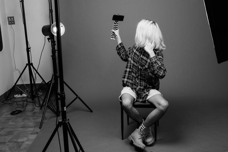 Midsection of woman photographing against gray background