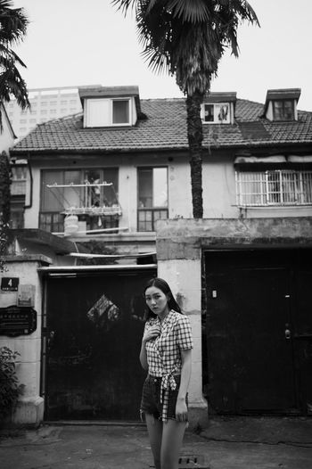 Portrait of woman standing against house in city
