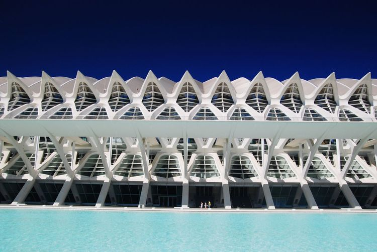 View of swimming pool and modern building against blue sky