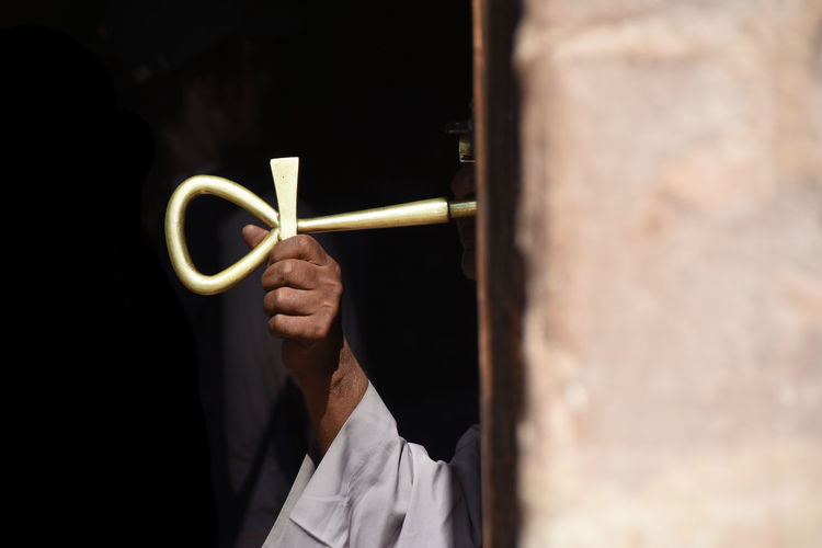 Man holding golden key to protect entrance Copy Space Egypt Entrance EyeEm Best Shots Gold Middle East Tradition Adult Clothing Dark Skin Doorway Egyptian Culture Headshot Holding Human Body Part Human Hand Key Lifestyles Lock Men Occupation One Person Protection Real People Selective Focus