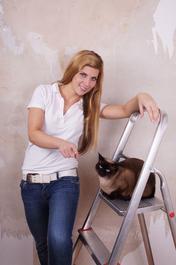 Portrait of smiling beautiful woman with siamese cat on ladder against wall
