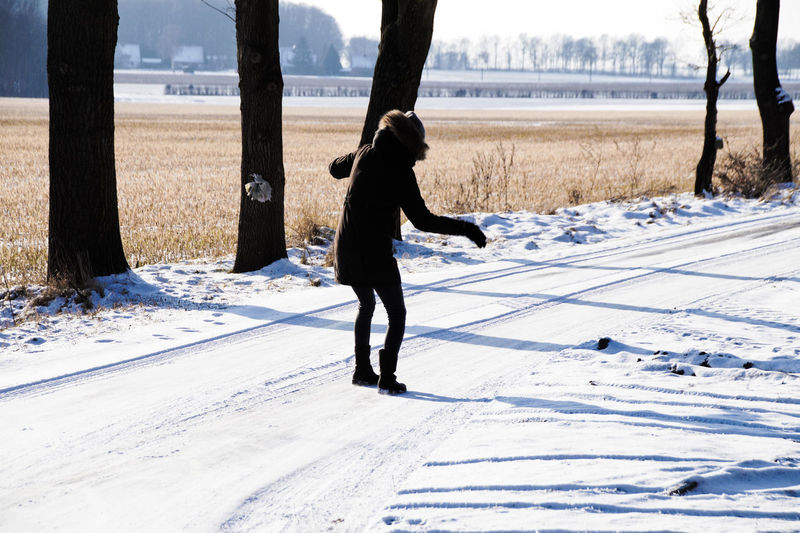Full length of woman standing on snow covered field against sky