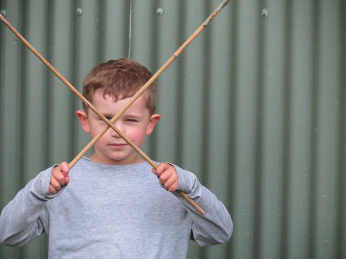 Close-Up Of Boy Playing With Sticks Against Corrugated Iron