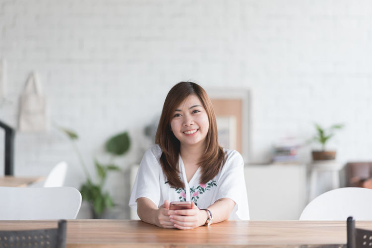 Adult Casual Clothing Communication Front View Hair Hairstyle Headshot Holding Indoors  Looking At Camera One Person Portrait Real People Sitting Smiling Table Wireless Technology Women Young Adult Young Women