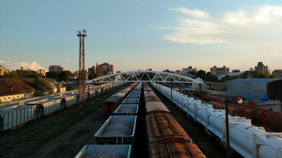 Railroad tracks amidst cityscape against sky