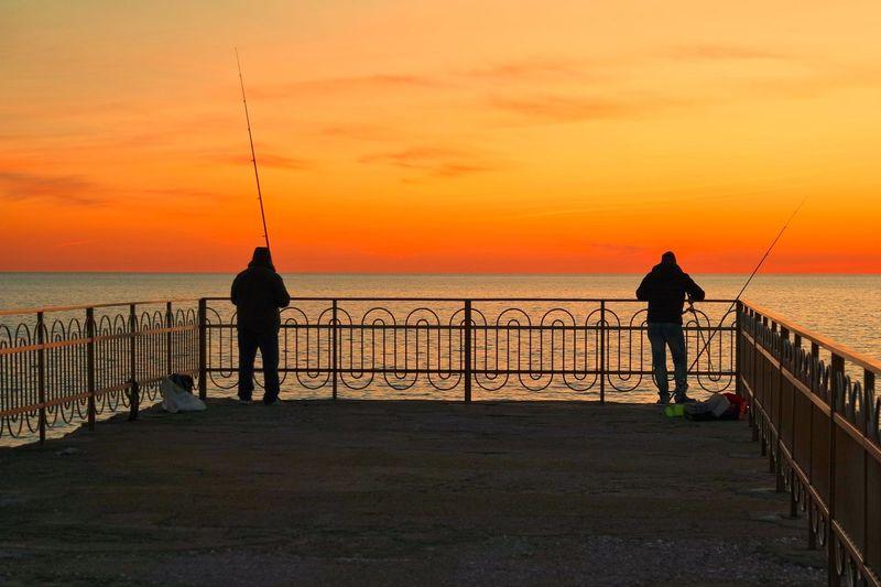 Silhouette men fishing on sea against sky during sunset