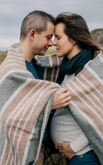 Pregnant woman with her husband embraced covered with a blanket on the field Autumn Couple Dad Family Field Happiness Love Maternity Mother Motherhood Mum Romantic Waiting Young Belly Blanket Embracing Father Future Outdoors Pregnant Togheter Tummy Two People Vertical