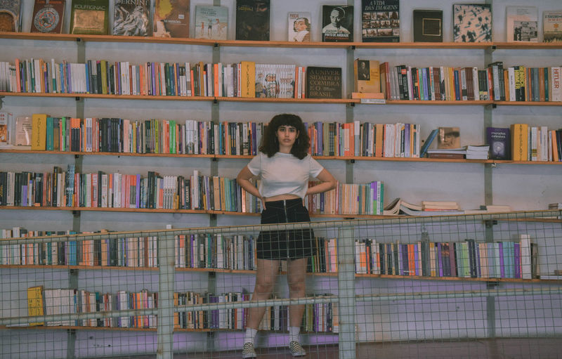 Shelf Publication Book Bookshelf Education One Person Library Front View Indoors  Learning Abundance Full Length Looking At Camera Portrait Adult Large Group Of Objects Young Adult Standing Women Hairstyle Studying