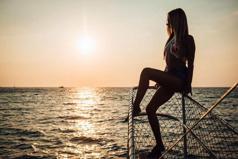 Water Sunset Sky One Person Sea Lifestyles Beauty In Nature Real People Scenics - Nature Young Adult Horizon Leisure Activity Young Women Sitting Horizon Over Water Nature Long Hair Full Length Women Hairstyle Hair Sun Outdoors Beautiful Woman