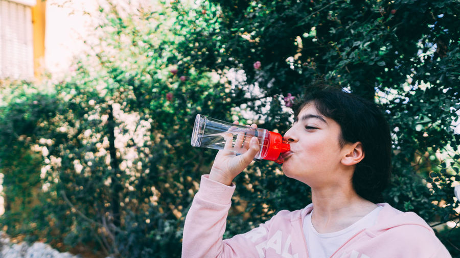 Girl drinking water from bottle against trees