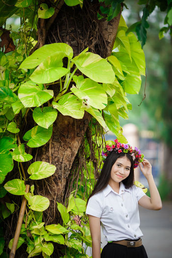 Portrait of woman wearing flowers while standing by tree