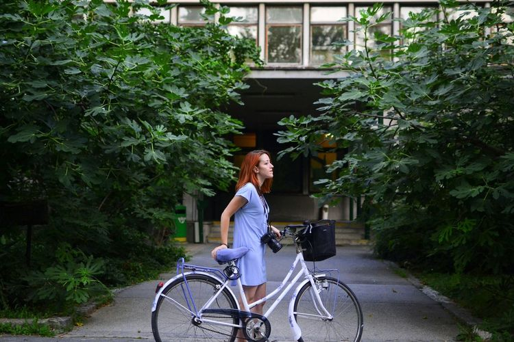 Young Woman With Bike In Front Of Apartment Building And Large Bush