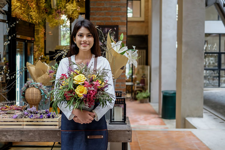 Portrait of smiling florist with flowers standing in store