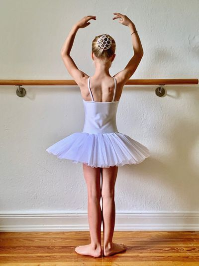 Rear view of ballet dancer with arms raised standing against wall