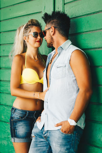 Young Adult Togetherness Casual Clothing Young Men Two People Sunglasses Three Quarter Length Standing Bonding Young Women Glasses People Fashion Real People Couple - Relationship Hair Wall - Building Feature Love Hairstyle Positive Emotion Outdoors Jeans