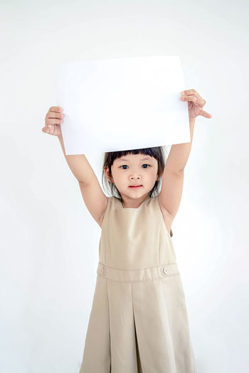Cute little girl with white sheet of paper. isolated on white background.