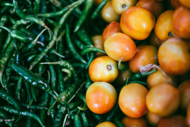 Close-up of tomatoes by green chili peppers