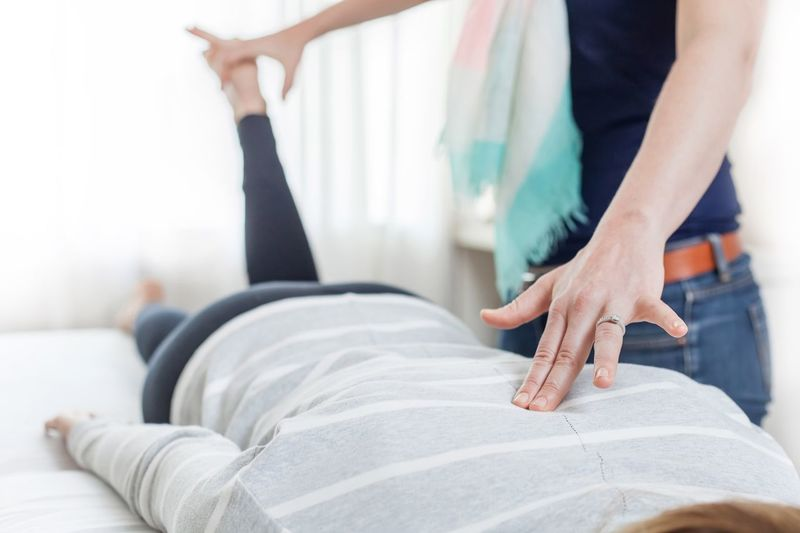 Midsection Of Physio Therapist Massaging Woman On Bed At Home