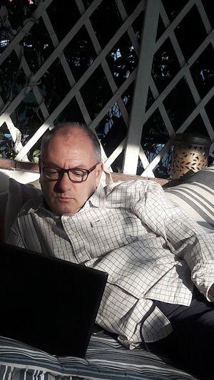 Full length of man sitting on mobile phone