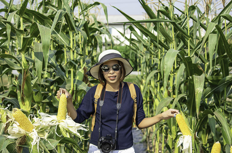 A woman holding the corn at the show in the farm. Growth Plant Front View Glasses One Person Standing Real People Young Adult Waist Up Green Color Nature Sunglasses Day Looking At Camera Land Agriculture Casual Clothing Field Plant Part Outdoors Fashion