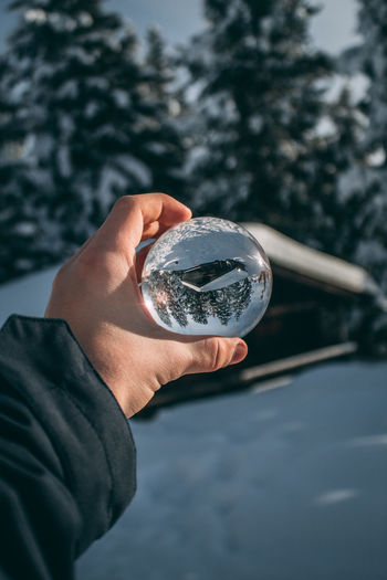 Close-up of person hand holding crystal ball on snow covered field during winter