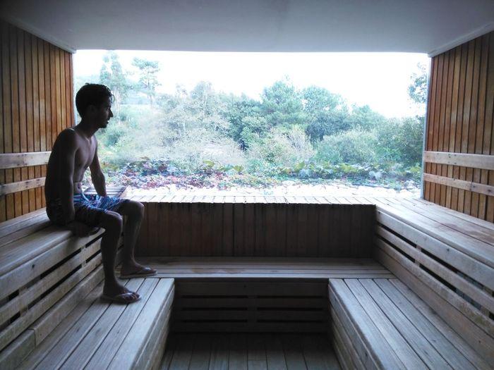 Shirtless Man Sitting By Glass Window In Sauna