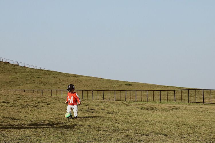 Rear view of boy walking on field