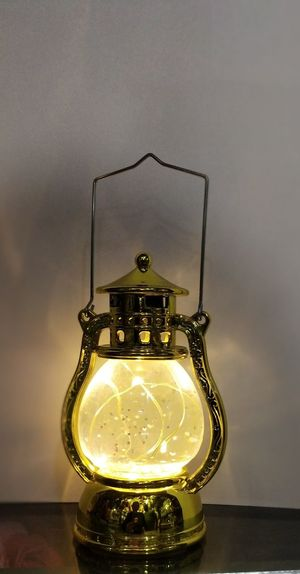 Close-up of illuminated light bulb on table against wall