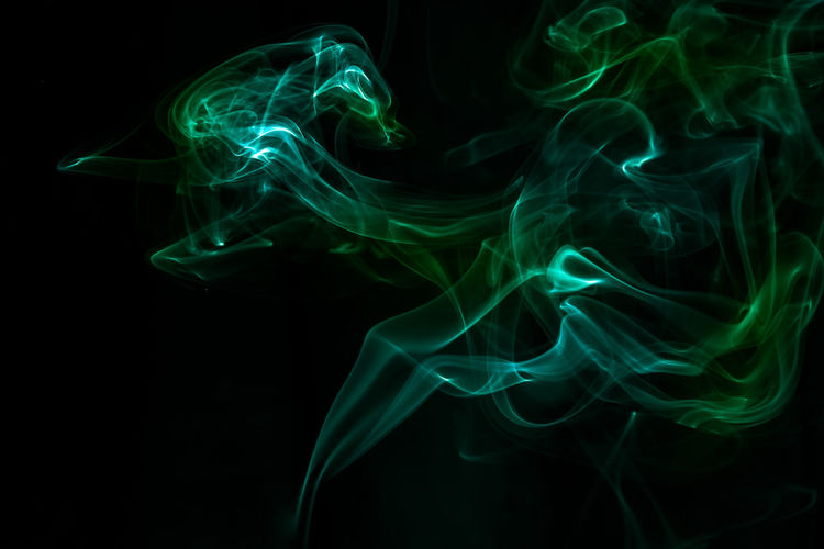 Green smoke against black background