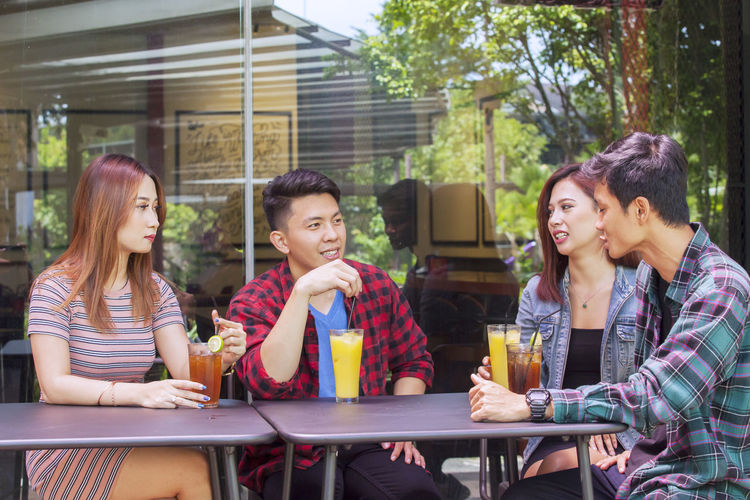 Friends talking while having juices at table