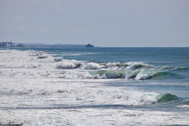 waves rolling in the ocean with the Newport Beach Pier in the background Sea Water Motion Wave Sky Beauty In Nature Horizon Over Water Scenics - Nature Horizon Land Beach Sport Aquatic Sport Surfing Nature Clear Sky Day Outdoors Power In Nature Newport Beach Pier Waves Pacific Ocean