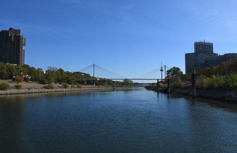 Bridge over river by buildings against blue sky
