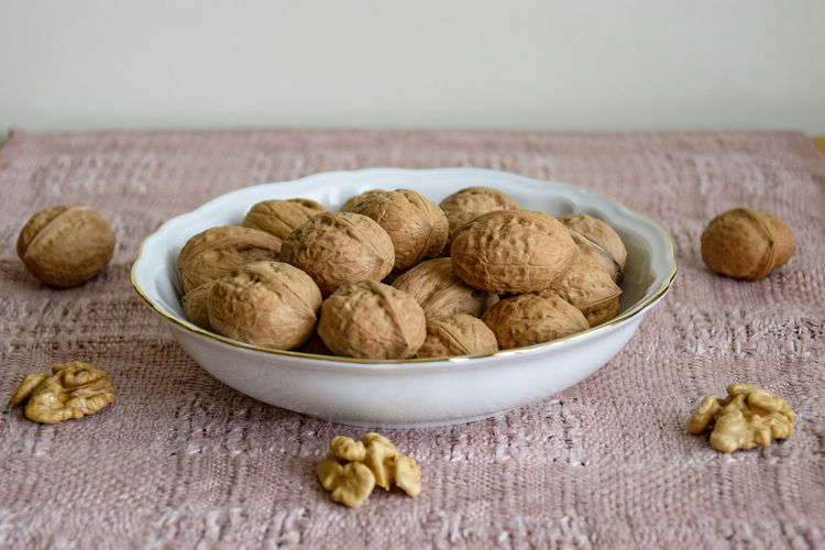 Walnuts in white plate on table covered with beige napkin, close-up, selective focus.