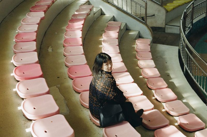 High Angle Portrait Of Woman Sitting On Seat At Theatre In Hangzhou Zoo